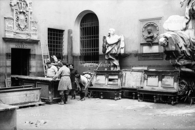 Florence flood of November 4, 1966: courtyard of the Museo dell'Opera del Duomo flooded; some men lead outside the flooded furnishings