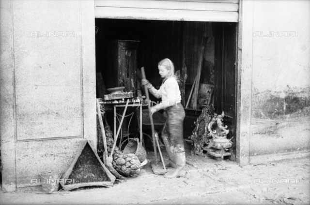 Florence flood of November 4, 1966: a girl cleans a flooded antique shop