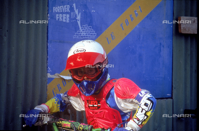 Photograph showing a motocross racer wearing a helmet and a suit. Suburb of Cerbaia, San Casciano in Val di Pesa, Florence.
