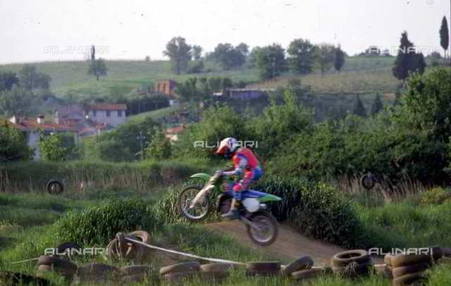 A motorcyclist jumping over a bump on a motocross track. Environs of Castelnuovo d'Elsa, Castelfiorentino, Florence