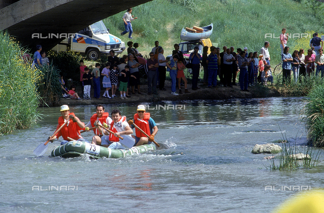 View of the river Elsa on which a competition of canoes is taking place, on the bank of the river, a crowd of people observing the event. Castelfiorentino