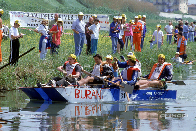 Stretch of the Elsa river during a canoe race. On the banks of the river some people are watching the event. Castelfiorentino.
