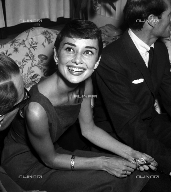 Audrey Hepburn during a press conference, smiling beside actor Mel Ferrer