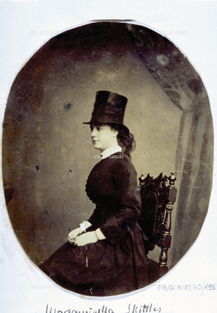 Three-quarter-length portrait of young woman in 19th century clothes and top hat