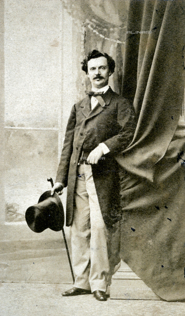 Full-length portrait of a young man in 19th century style day dress. He is holding a top hat in his right hand and a stick in his left