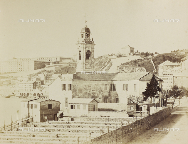 Panorama of Genoa. In the foreground a few houses and a bell tower. On the left, a stretch of coast can be glimpsed