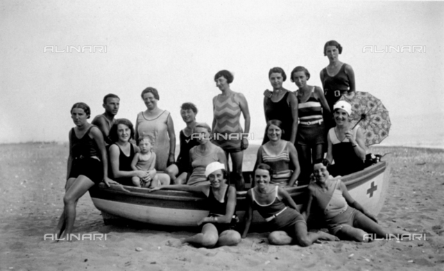 Portrait of a group of women in bathing costumes on the beach at Marina di Massa. A few of them are sitting in a boat, the others are standing around it. Among them is a small boy and young man