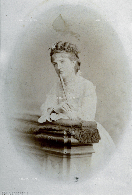 Studio portrait of queen Margherita. Taken on the occasion of an official visit to Venice, it shows the queen leaning on a balustrade, and hHolding a closed fan