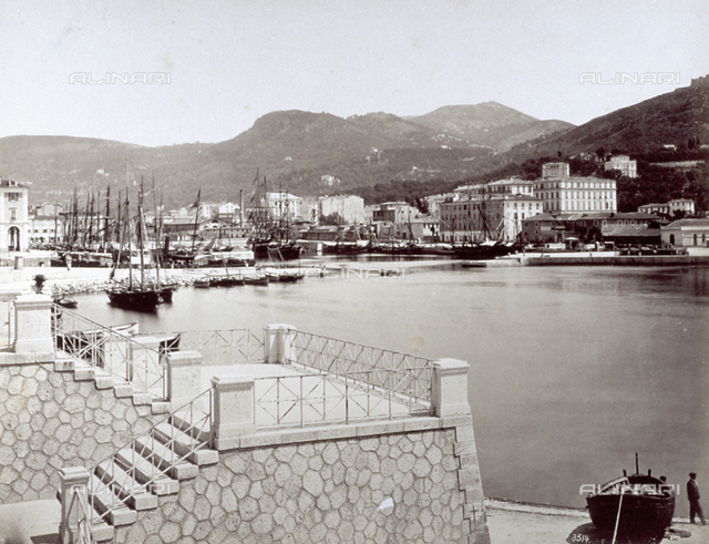 The port of Nice with numerous sailboats, in the foreground, on the right, a boat drawn up on the beach. On the left a terrace. In the background, the hills which surround the city