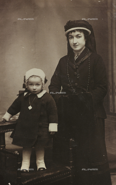 Portrait of a young woman in elegant widow's dress with her small daughter