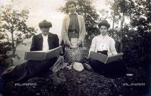 Portrait of three young ladies in a wood. The woman at the center is kneeling on the grass, holding a straw bag and a book. The other two ladies are seated on the grass leaving through a book