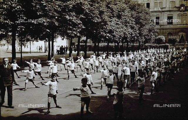 A group of young fencers shown practicing outside. In the background rows of trees and buildings