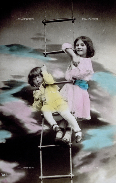 A little boy and a little girl playing on a rope ladder. He is seated on a rung and the little girl is standing behind him