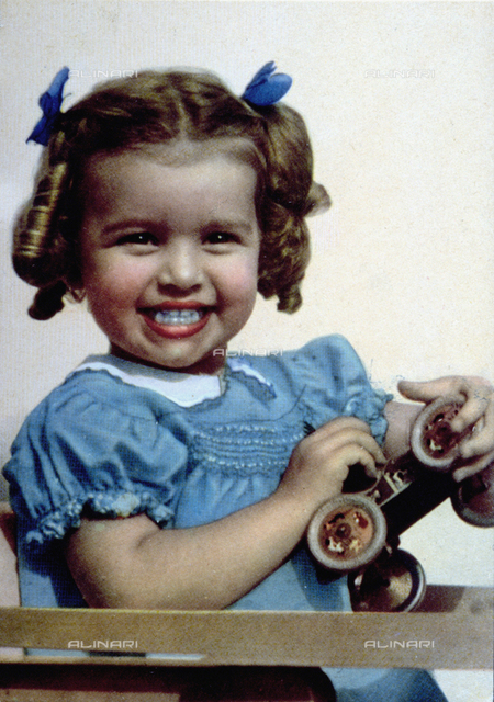 Half-length portrait of a little girl seated on a high chair. She is smiling and holding a toy car