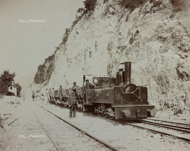 Work scene. In the foreground a small locomotive pulling a few mining carts. On the rock wall, behind the train, a few workers are working. On the carts other workers are posing for the photograph