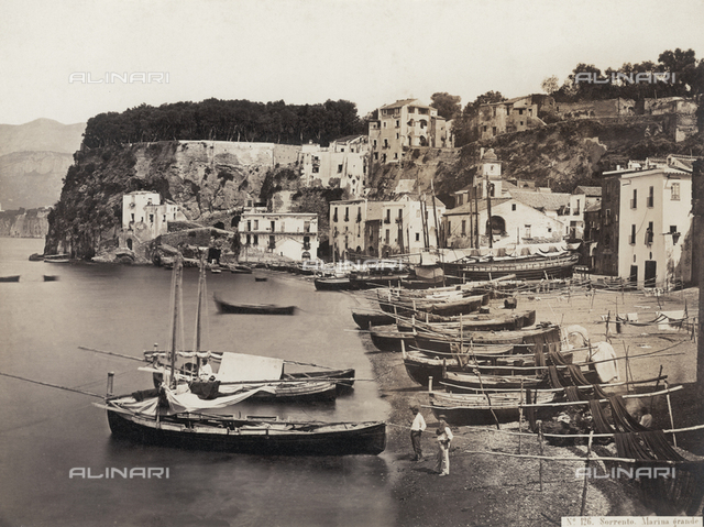 Panorama of Sorrento. In the foreground the marina with boats drawn up on the beach and nets laid in the sun. In the background the white houses of the town and the typical rocky coast