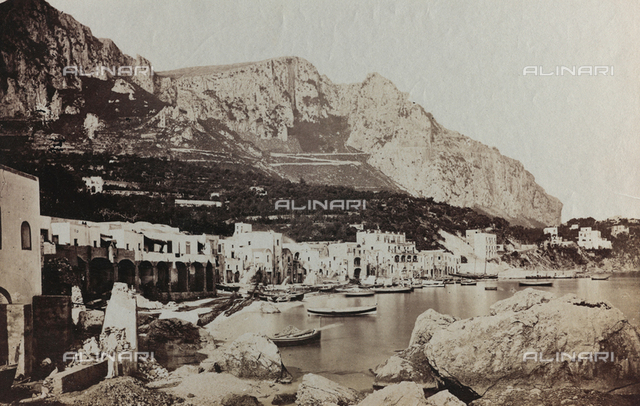 View of Marina Grande in Capri. In the foreground the typical houses of the town, overlooking the stretch of sea where a few boats are ied up. In the background, hilly landscape with rich vegetation. The figure of a man can be seen on the left