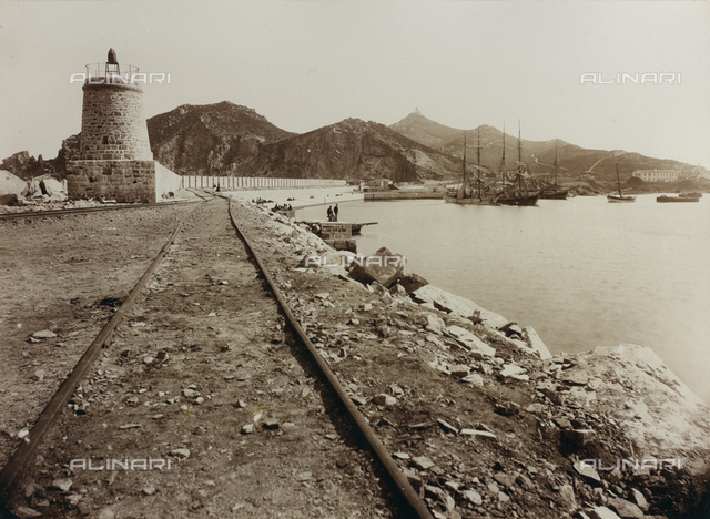 The Port of Tortolì, in the province of Nuoro, with sailboats lying at anchor. In the foreground, the tracks of a railroad in construction flanked by a stone tower