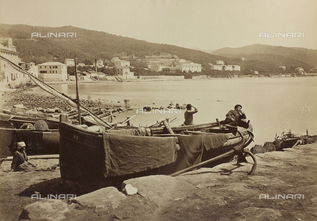 The marina of San Remo with boats drawn up on the beach. On the water's edge, a fishing boat: on the stern a young man lying down, on the prow clothes and blankets spread out in the sun