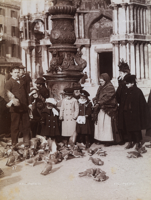 Men, women and children feeding the pigeons in a piazza in Venice