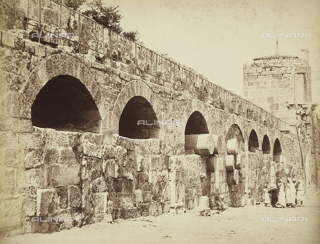 View of the city walls of Heliopolis or Baalbek, ancient Syrian city, now Lebanon. A group of people are gathered together close to the wall