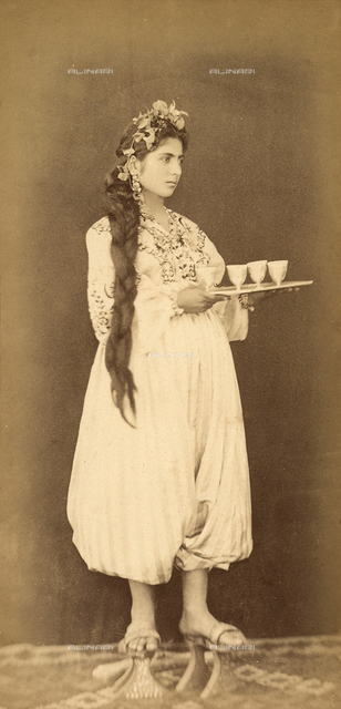 Turkish woman with long hair and wooden platform shoes, carrying a tray with four glasses