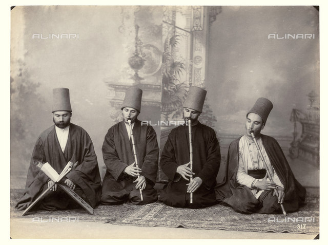 Three Dervish musicians and singer performing while seated on some carpets