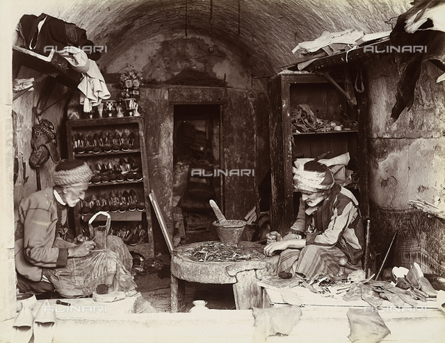 Two Turkish shoemakers working inside their workshop