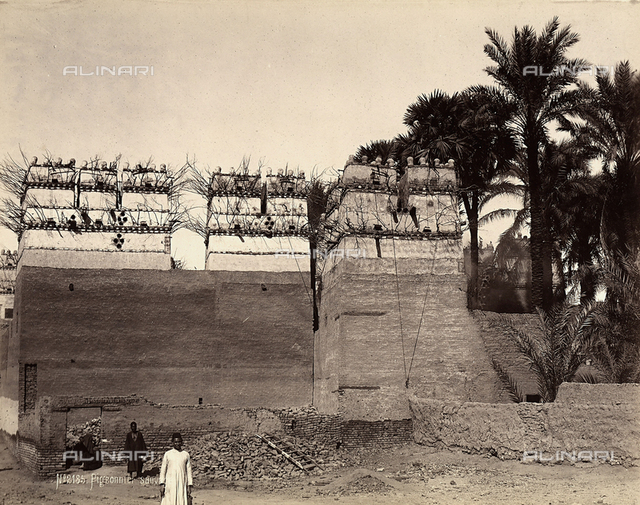 Some men in front of a fortified structure whose upper section is used as a pigeonhouse
