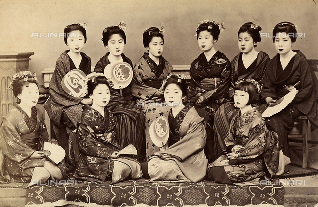 Group portrait: Japanese women in kimonos with traditional fans.