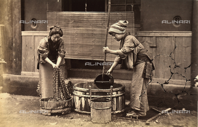 Two Japanese women pouring water into a large wooden tub, used for washing laundry.