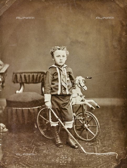A child dressed as tamer circus with a horse-toy on wheels