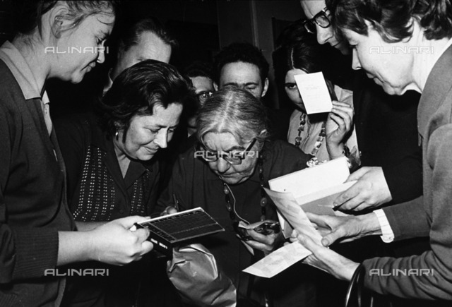 A female Russian writer signing autographs
