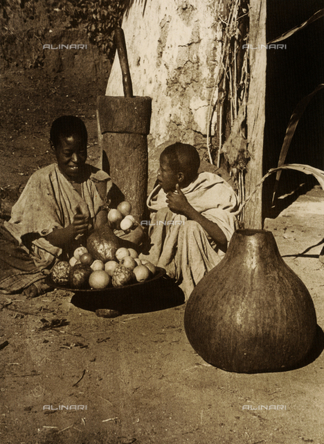 Fruit vendors in front of a hut; behind them is a churn and in front a squash