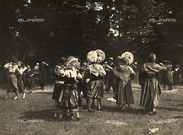Women in traditional Piedmont costume dance at a country festival