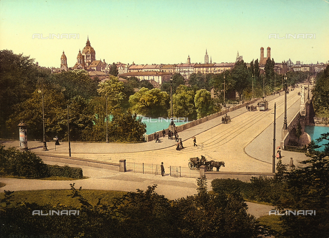 View of the city of Munich, with a bridge crossed by people, carriages and busses in the background.
