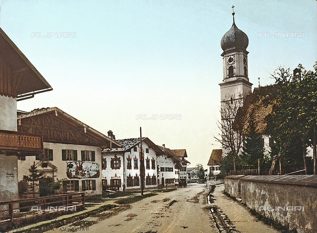 Some houses and the bell tower of the church, along a road of Oberammergau, in Germany.