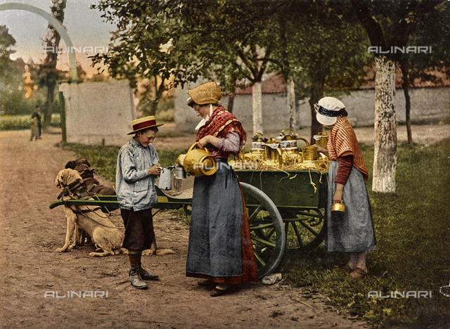 Milk Sale: two ladies in traditional dress of Brussels pour some milk for a child, who is close to their cart pull by dogs.