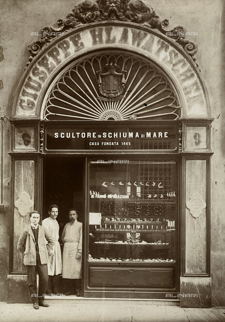Sign and window of a shop with sepiolite sculpture. At the entrance door: two people in work clothes together with a man