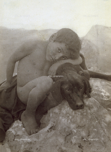 Portrait of a naked child tenderly embracing a dog which lies down on stone