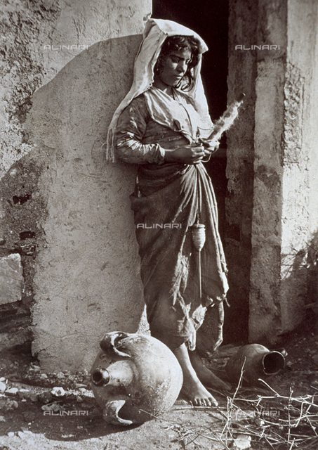 Full-length portrait of a native child in traditional costume. The young girl, leaning against the wall of a dilapidated building, appears to be engrossed in the act of winding wool. An amphora is lying on the ground in the forefront
