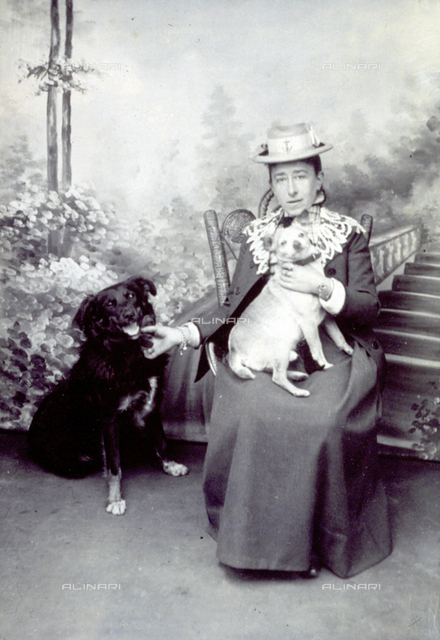 Studio portrait of a woman. She is sitting, with a dog in her arms and another dog is sitting by her side
