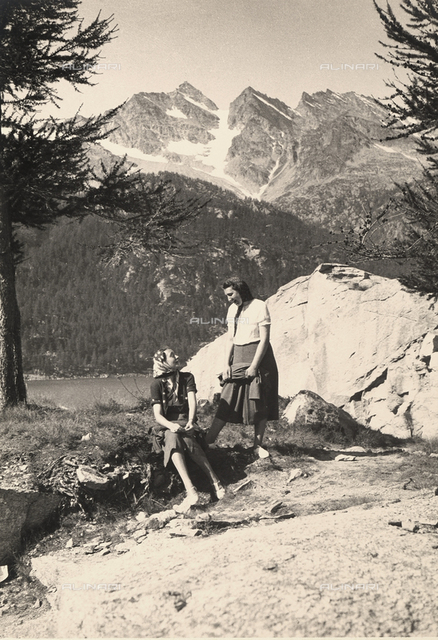 Two women converse in a mountainous landscape