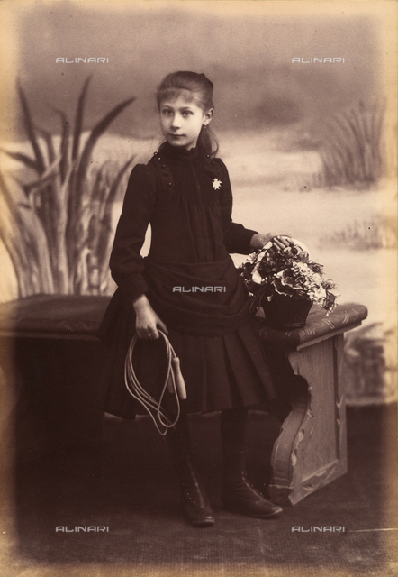 Full-length portrait of a girl with a basket of flowers