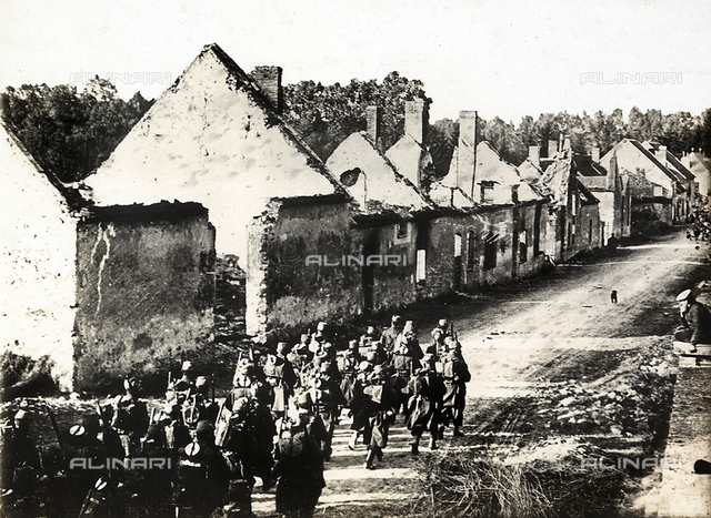 A squad of French infantry soldiers marches on the Germans, crossing a destroyed village.