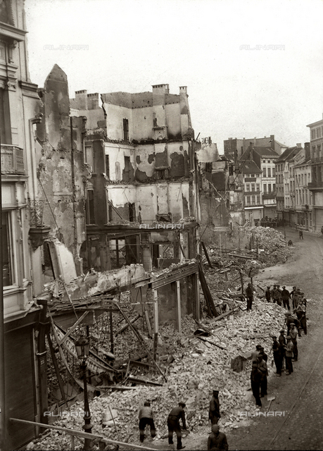 The image shows the effects of German bombardments on the city of Antwerp. Many buildings have been bombarded and a group of people digs among the ruins.