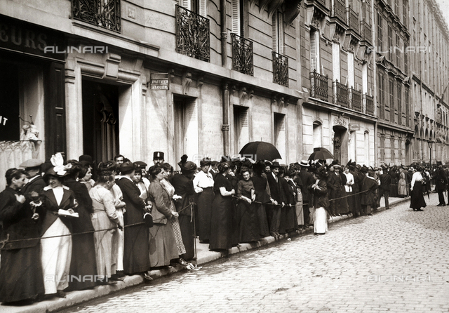 The image shows many people in a line in front of the offices of the savings bank in Rue Bounit Romains, to draw their savings for the living-on during the war.
