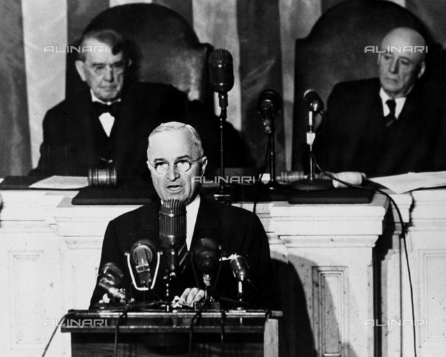 The President of the United States, Harry Spencer Truman, portrayed while delivering a speech, before the session of the 81st Congress. Behind the President, Kenneth McKellar, Senator of Tennesse (on the right), and Sam Rayburn, Representative of Texas, can be seen.