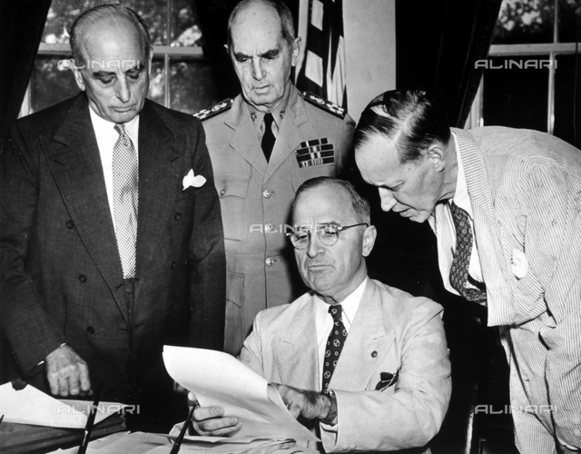 The President of the United States, Harry Spencer Truman, reads a document, sitting near a table, in presence of an officer and of two politicians.
