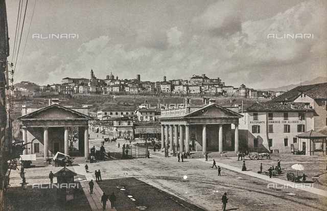 View of a square of Bergamo, with two propylaea and various passer-bys. In the distance, the old town is visible.